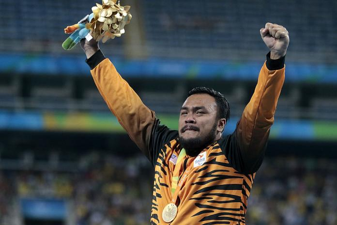 Gold medalist Muhammad Ziyad Zolkefli of Malaysia celebrate on the podium at the medal ceremony for the Men's Shot Put F20 Final at the Rio 2016 Paralympic Games.